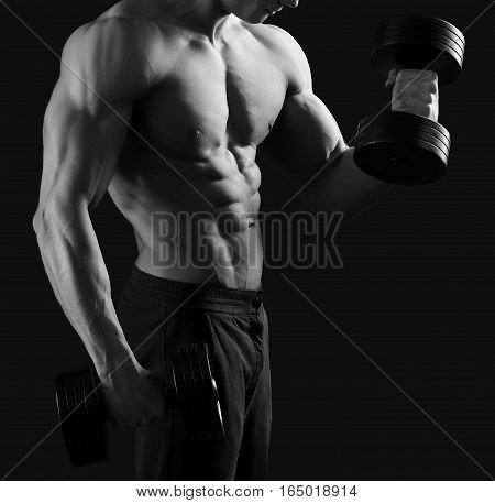Exercise equipment. Black and white cropped shot of a muscular fit and toned fitness man lifting dumbbells