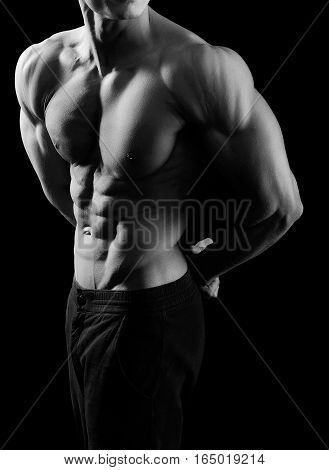 Such a body takes work. Monochrome cropped shot of a sexy ripped muscular man posing in studio showing off his abs