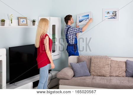 Young Woman Showing Male Carpenter For Hanging Picture Frame On Wall At Home