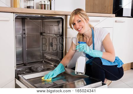 Young Woman Cleaning Dishwasher With Rag And Spray Bottle In Kitchen