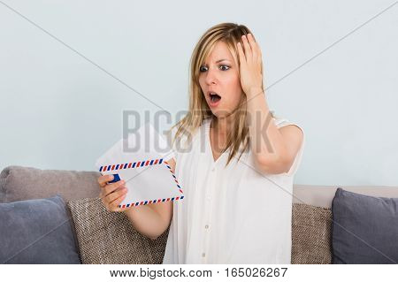 Portrait Of A Sad Young Woman Reading Letter