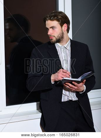 handsome young fashion bearded businessman with stylish hair in classic suit standing near window with black notebook and pen on white wall background