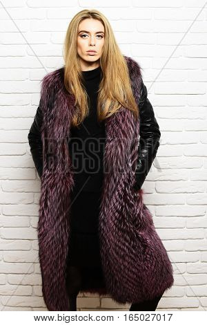 young fashionable sexy pretty woman or girl with beautiful long blonde hair in waist coat of burgundy fur with black leather sleeves and fashion makeup on white brick wall studio background
