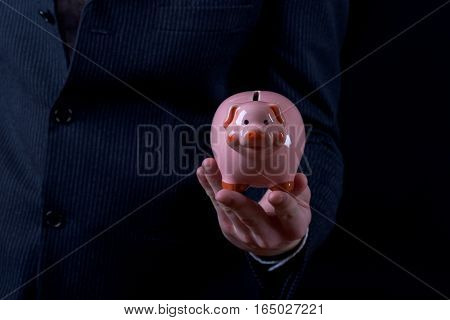 Businessman in elegant suit with piggy bank in hands. Banking and financial savings concept.