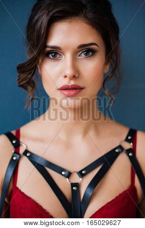 Emotional Portrait of a Beautiful woman wearing seductive lingerie and leather accessories. Professional make-up and hairstyle. Perfect body and skin. Fashion photo. Sweet fetish. Natural beauty.