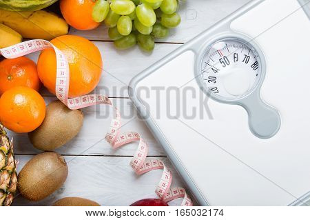 Stack Of Fruits, White Weight Scale And Tailor Meter On Wooden Board. Concept Of Diet And Healthy Li