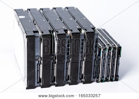 stack of old hard drives on white background