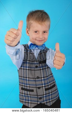 Schoolboy showing two thumbs up isolated on a blue background