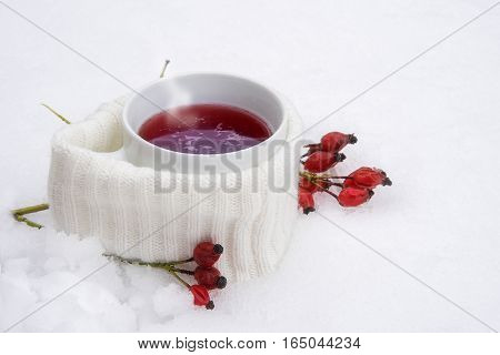 Hot red tea in the snow cup with scarf and rose hips white snowy background with copy space hot drink against flu selective focus narrow depth of field