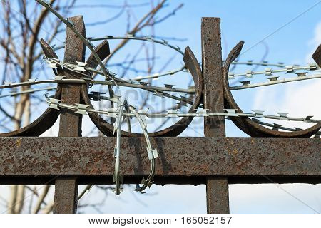 Metal fence with barbed wire against the sky. Macro shot.