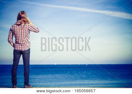 Man By Seaside Receiving A Call On His Phone