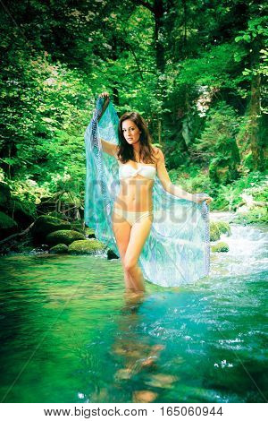 a young beautiful lady is posing in a river flowing through the forest