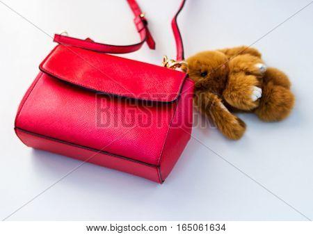 Red ladies handbag ladies handbag with a soft toy.