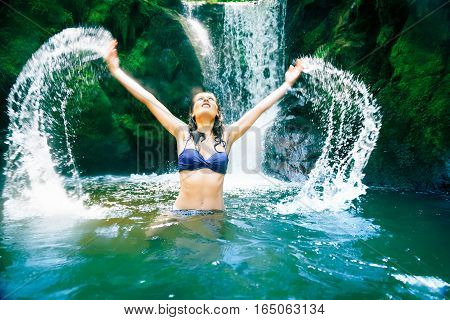 a young beautiful lady is enjoying the waterfall's cold water
