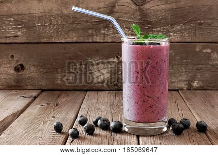 Healthy Blueberry Smoothie In A Glass With Berries, Mint And Straw Against A Rustic Wooden Backgroun