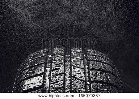 Studio shot of a set of summer, fuel efficient car tires on black background. Covered in wated droplets, rain or aquaplaning concept. Contrasty lighting and shallow depth of field