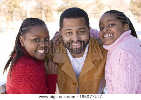 Portrait of an African American father and his daughters.
