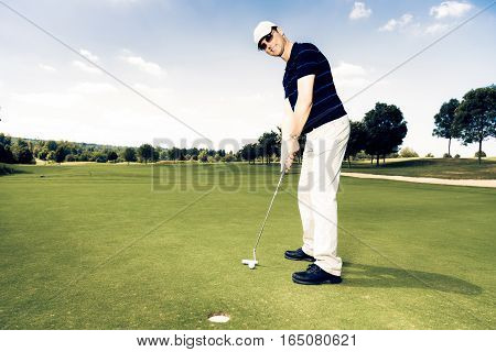Adult male golf player putting on the green.