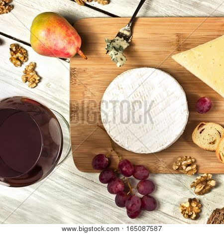 A square photo of a tasting with two glasses of wine, red and white, different types of cheese, bread, nuts, pear, grapes, on a wooden board