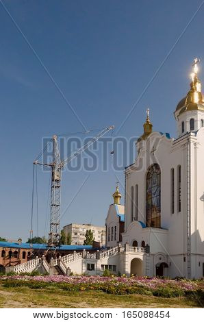 Building Christian orthodox white church with gold domes and crosses by construction crane