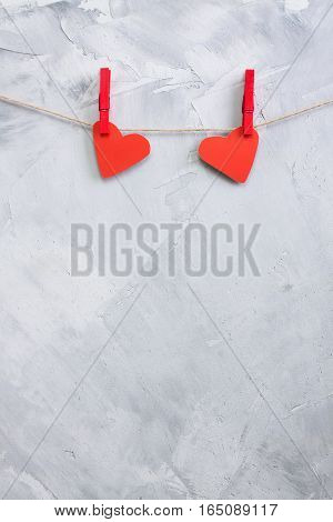 Two Red Paper Hearts Hanging Onto Clothespins On A Rope.