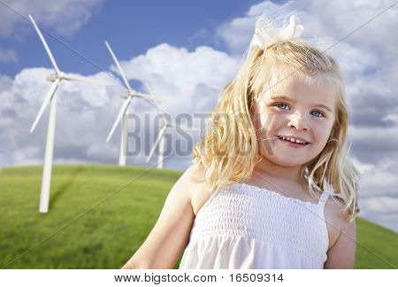 Beautiful Young Girl Playing Near Wind Turbines and Grass Field.