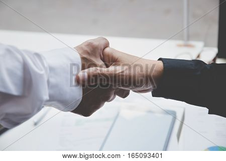 businessman handshaking in office - teamwork cooperation agreement acquisition concept (blur for background)