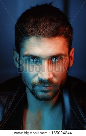 Man in leather jacket. Piercing eyes. Husky eyes. Dramatic portrait of tinted red and blue filter. Fashionable style.