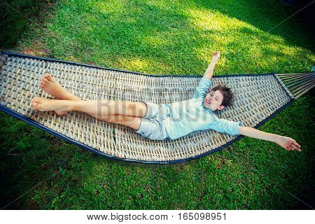 Cute little boy relaxing in a hammock during summer vacation on beautiful warm day