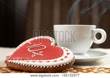 Full of joy. Cup of warm coffee steaming next to a gingerbread glazed cookie