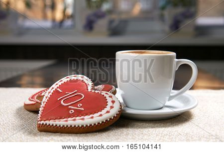Cup of coziness. Closeup shot of red glazed Valentine s day cookies near a cup of delicious cappuccino