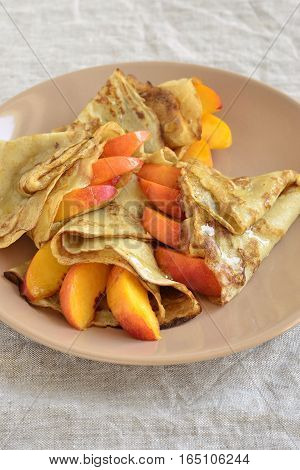 Delicious pancakes with peaches and honey for breakfast, vertical