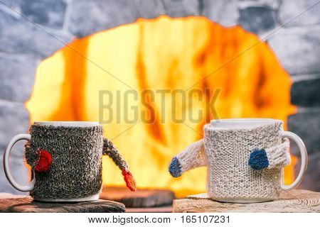 Tea mugs in sweater cozies on the rustic table. Fireplace on the background