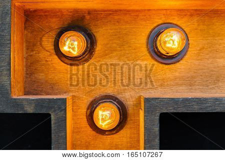 Light bulbs in a wooden recess. Retro style decor element. Glowing bulb. Part of the wooden object. Electric light orange