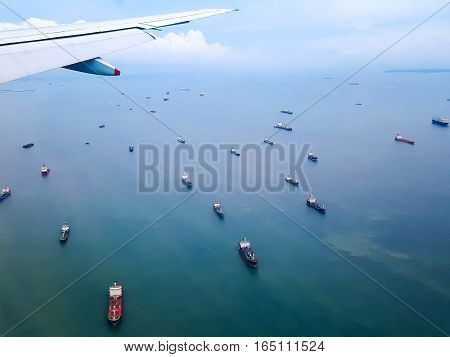 Many cargo ships float in the sea the view from the window of a plane.