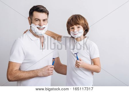 I will teach you. Handsome young father and his teenage son with shaving foam on their faces wearing white T-shirts looking at camera standing against white background