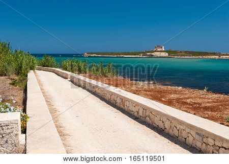 Road along the coastline in Portopalo (southern Sicily); the island of