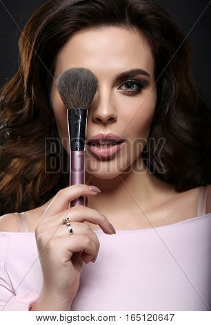 Gorgeous Woman With Dark Hair Finishing Her Makeup Using Powder Brush