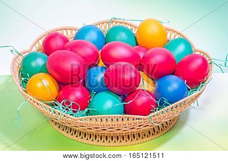 Vibrant Colored Easter Eggs In A Brown Basket, Gradient Background, Close Up.