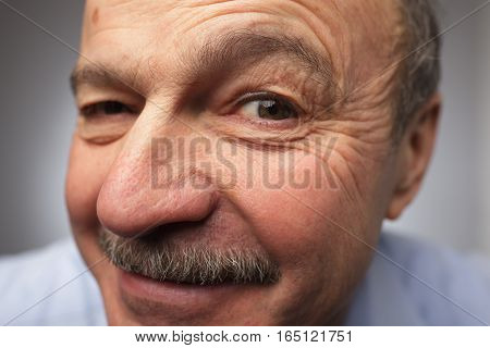 Man with mustache looking at the camera winking keeping secret