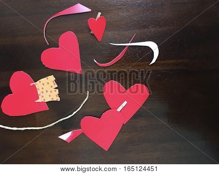Whimsical Hand Made Red hearts photo on wood background cut out for Valentine's Day February 14 social share or promotional background image with room for copy or to add hashtag for event, invitation or conceptual message about love and community