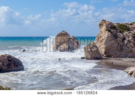 Aphrodite's Rock, Cyprus, shot in late summer and shows large waves crashing onto the large rocks. A few people on the beach show the scale of the rocks.