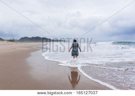 Woman walking exploring beach ocean coastline with rain clouds on horizon