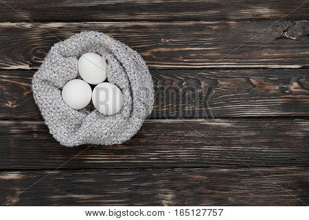 Three eggs in knitted scarf looks like nest. Easter or paschal symbol