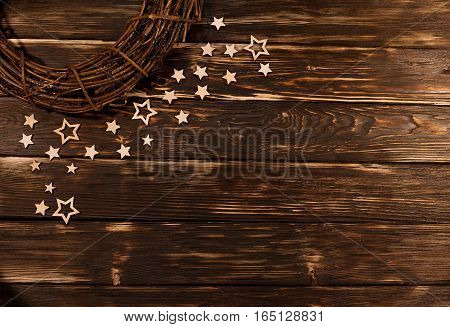 Christmas wreath with wooden stars on wooden rustic background. With empty place