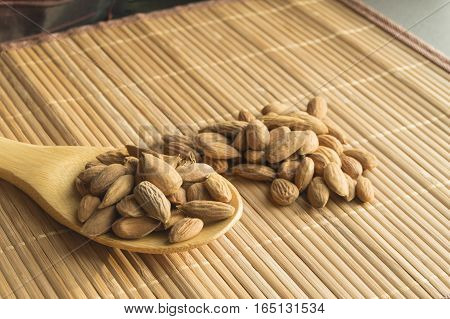 Wooden spoon with almonds on a bamboo napkin.