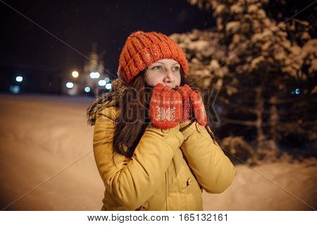 the girl's portrait against the background of the evening city which has frozen and warms in the winter hands. in the light of city lamps.