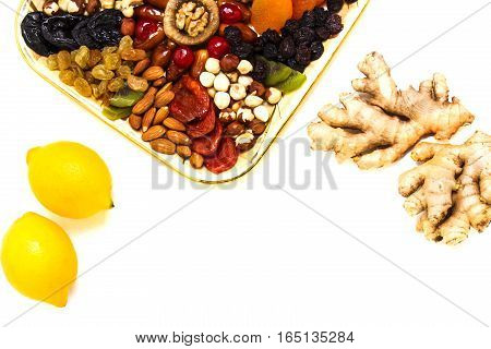 Lemon, ginger and healthy snack foods on white table. Close up. Top view. Copy space for text