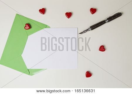 Green envelope, message, pen and small red hearts on white table. Top view. Love letter, valentines day concept
