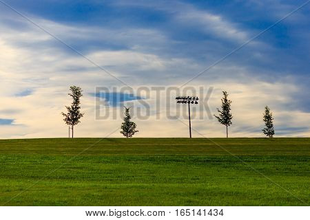 Stadium lights with blue and white sky.